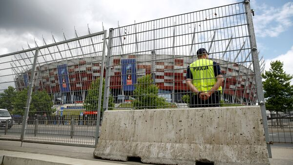 Polish police officer stands guard in front of the PGE National Stadium, the venue of the NATO Summit, which will start in two days, in Warsaw, Poland, July 6, 2016. - Sputnik Грузия